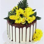 torty okolicznościowe białystok - brązowy drip z żółtymi kwiatami