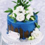 torty okolicznościowe białystok - niebieski drip z białymi kwiatami